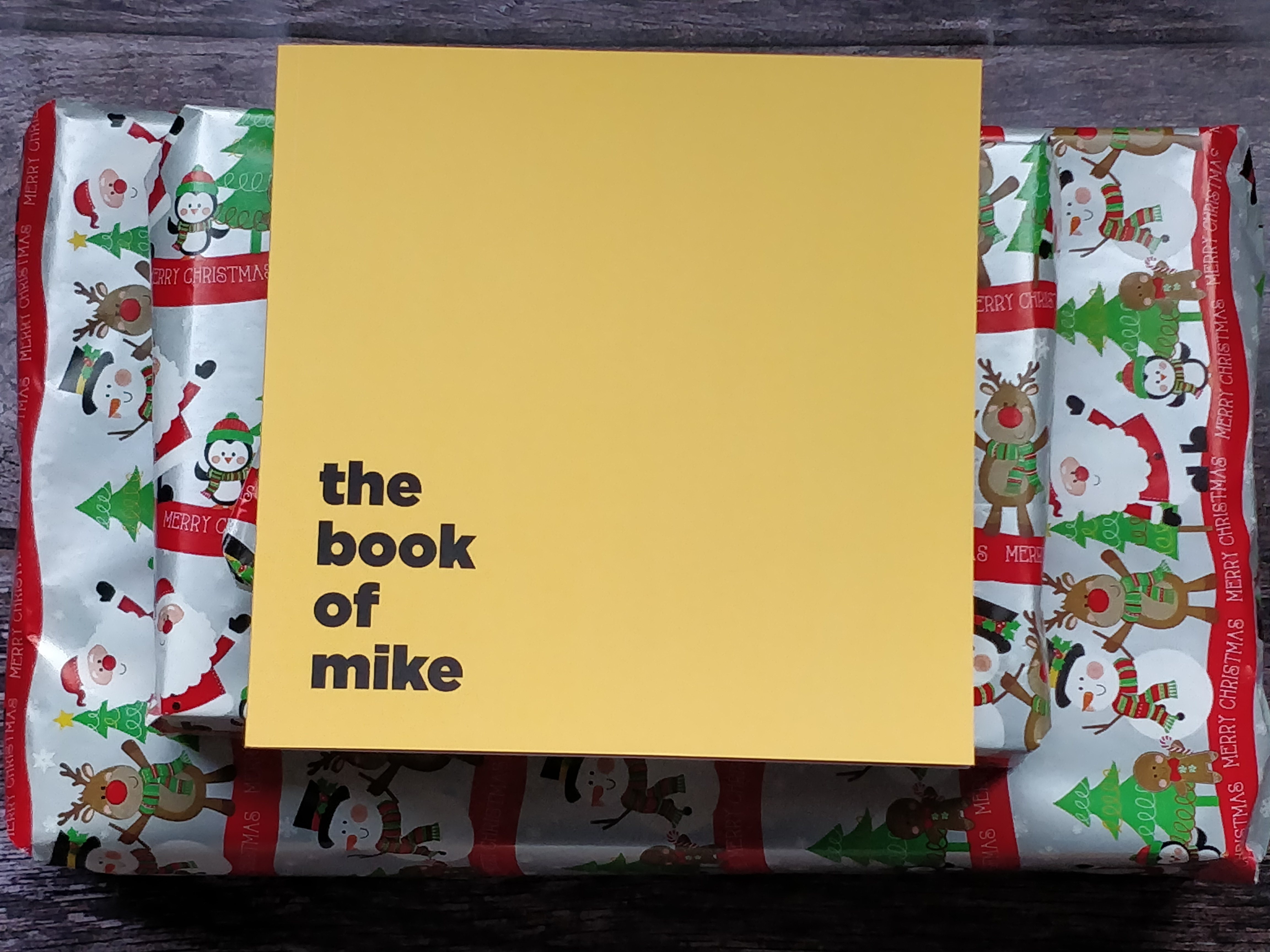 A yellow thin book on top of a pile of presents wrapped in silver and red wrapping. The book says The Book Of Mike on it.