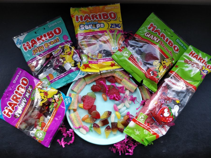 5 packets of vegetarian haribo sweets around a light blue plastic plate with various haribo sweets on it.