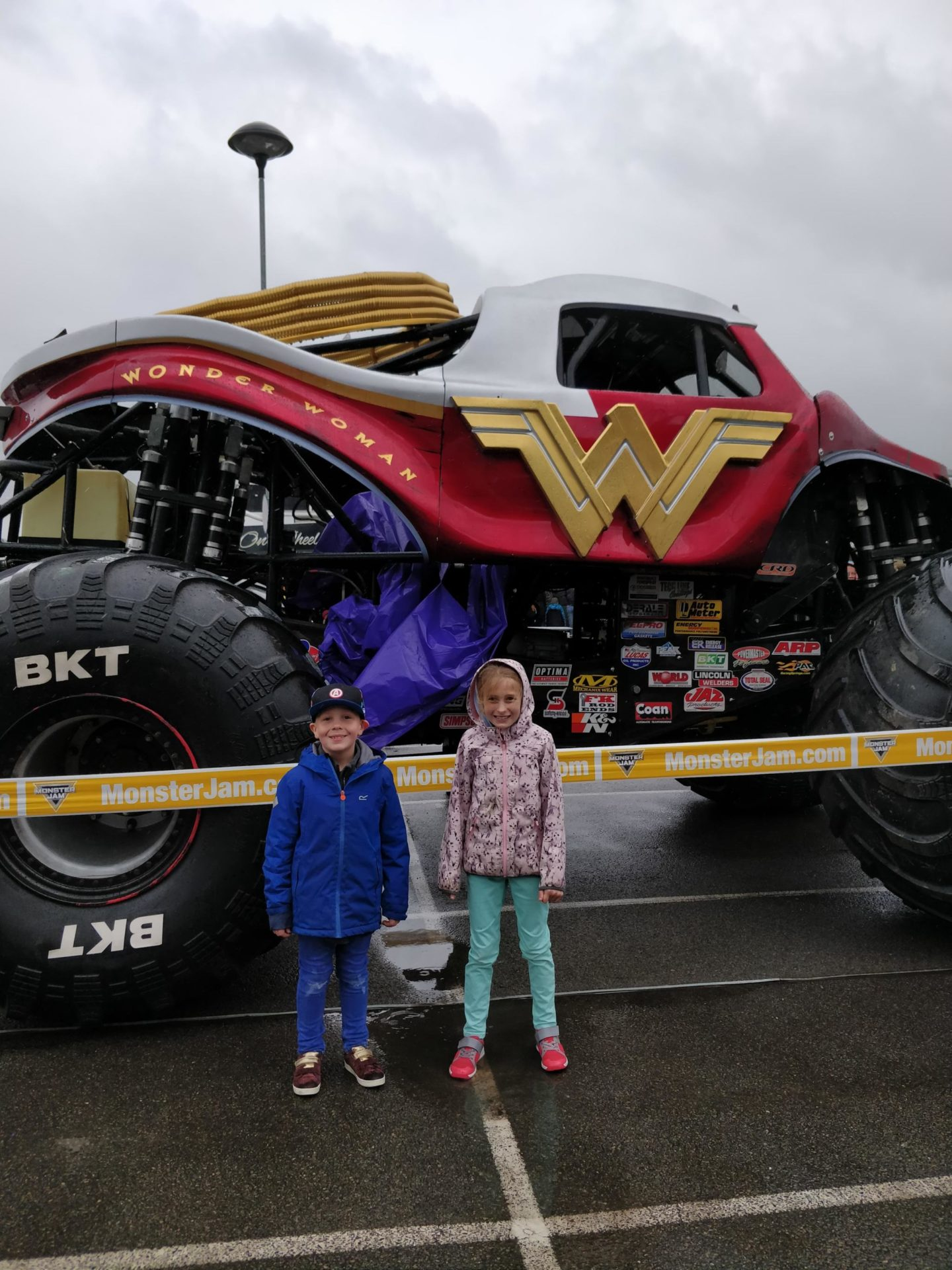 Two children standing in front of a Monster Jam truck.