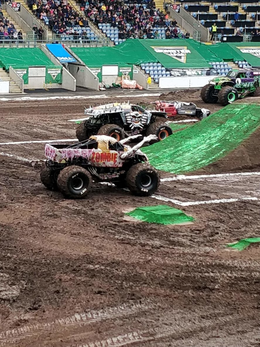 Four Monster Jam trucks in a muddy arena.