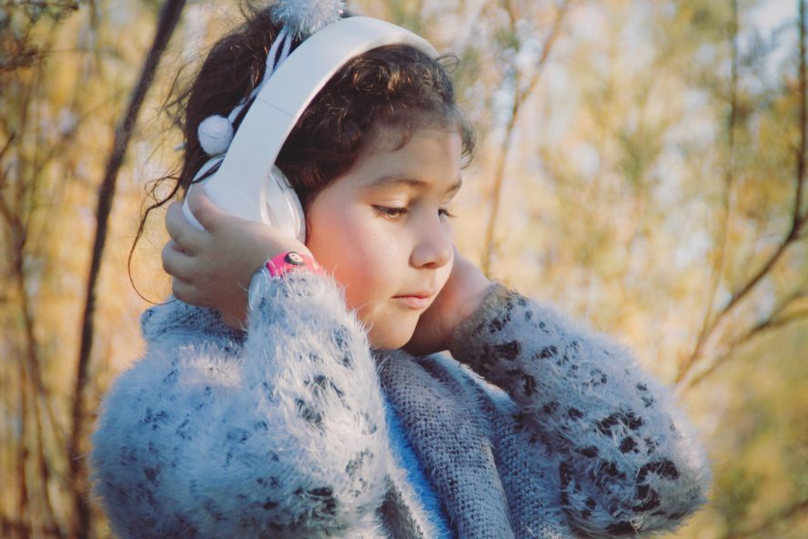 Little girl wearing headphones outside